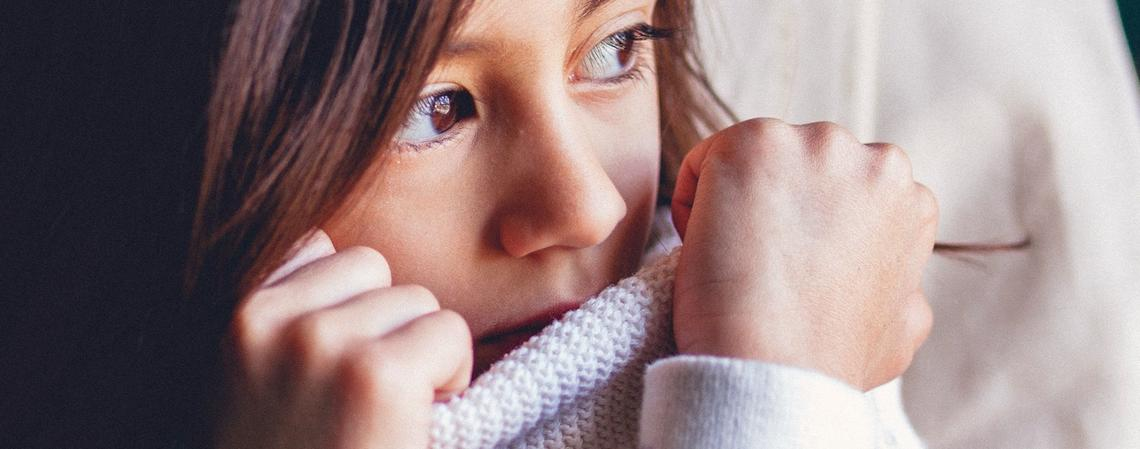 child wearing sweater covering face