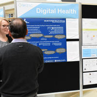 Students look at a poster presentation for eHealth