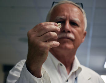 Researcher looking at a pill