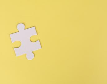 White puzzle piece on a yellow background